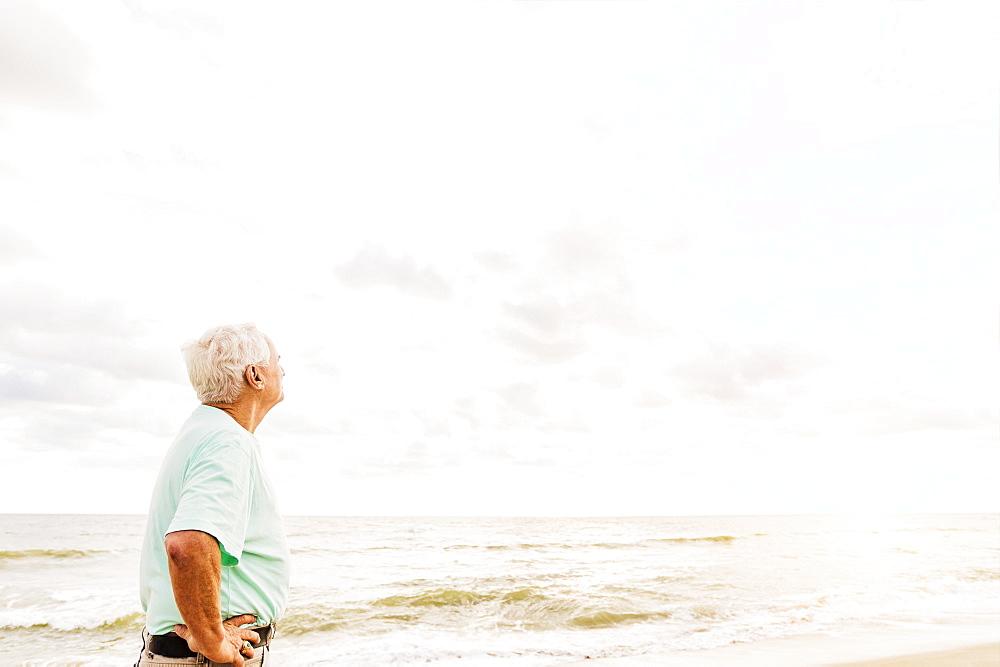 Side view of senior man standing on beach, Jupiter, Florida