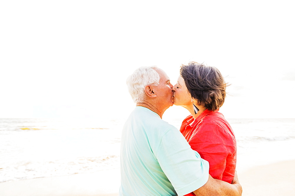 Older couple kissing on beach at sunrise, Jupiter, Florida