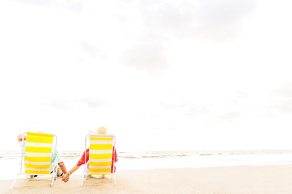 Rear view of couple sitting in lounge chairs on beach, Jupiter, Florida
