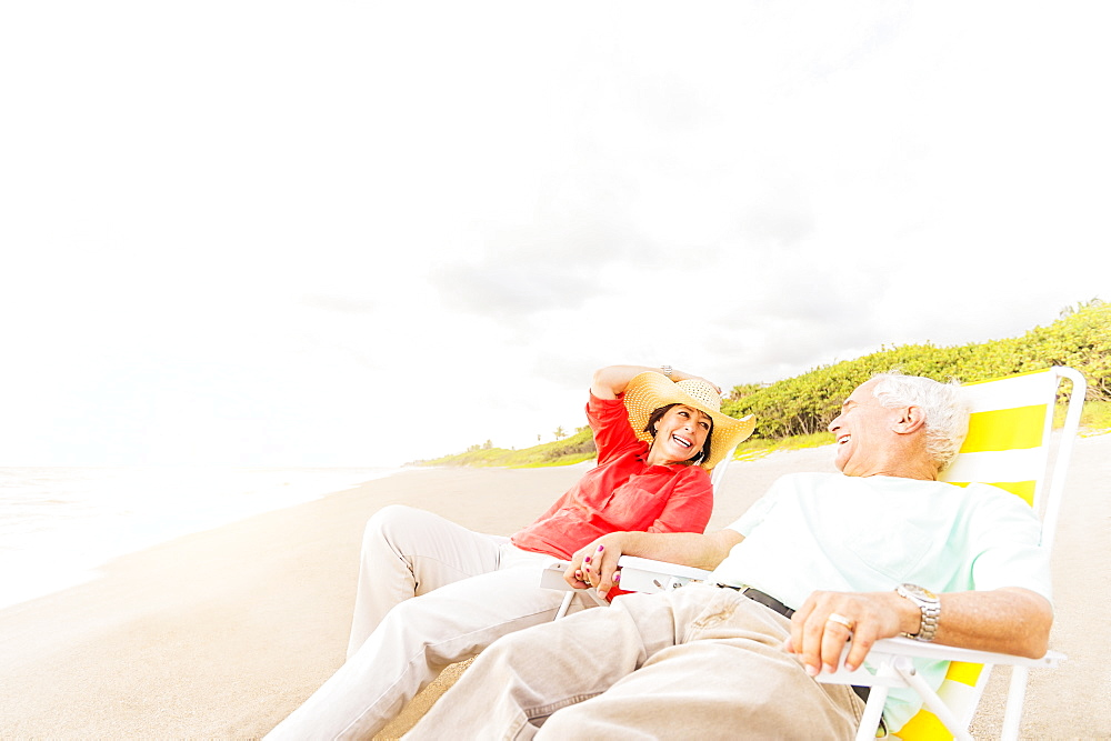 View of couple sitting in lounge chairs on beach and laughing, Jupiter, Florida