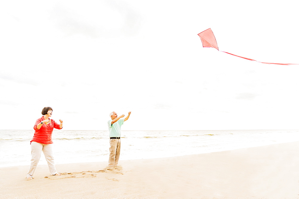 Couple flying kite together on beach, Jupiter, Florida