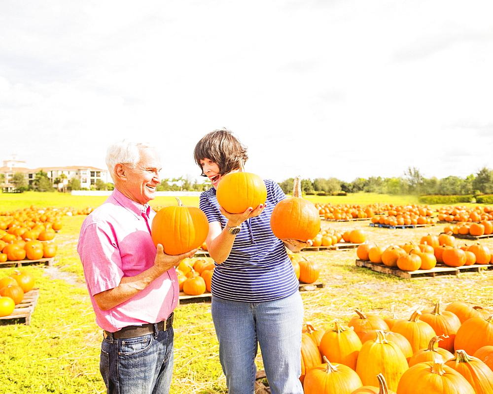 Couple talking and holding pumpkins, Jupiter, Florida