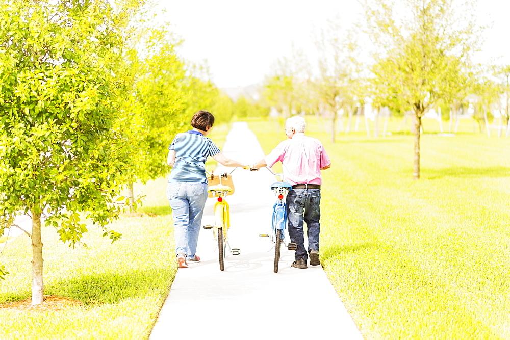 Rear view of couple wheeling bicycles along cycling path, Jupiter, Florida