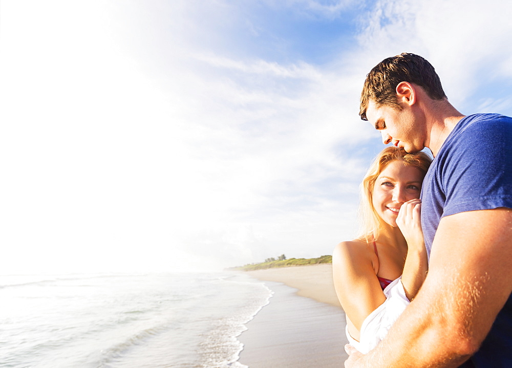 Portrait of young couple embracing on sandy beach, against background of coastline, Jupiter, Florida