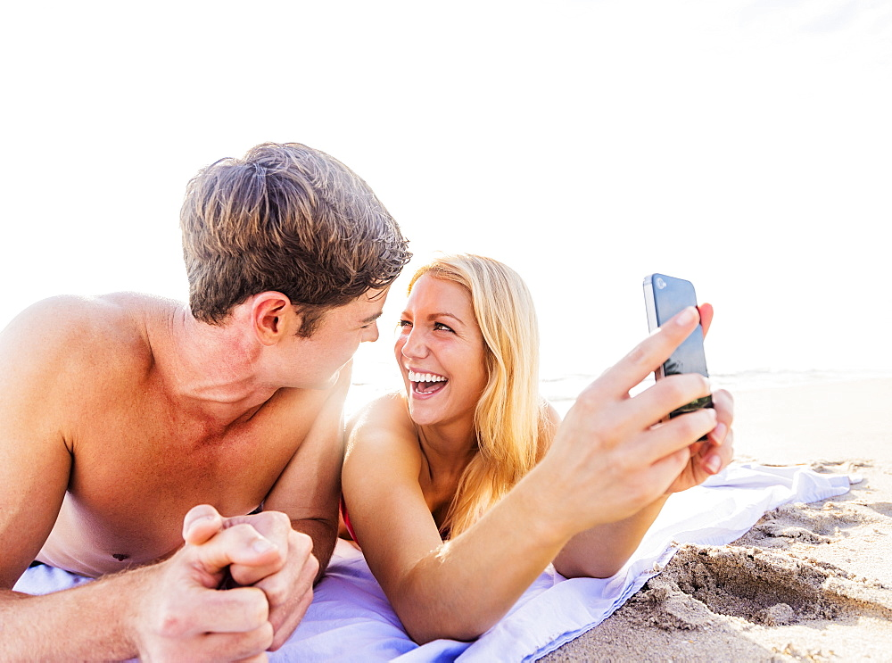 Portrait of young couple lying on blanket on beach, using smart phone, Jupiter, Florida