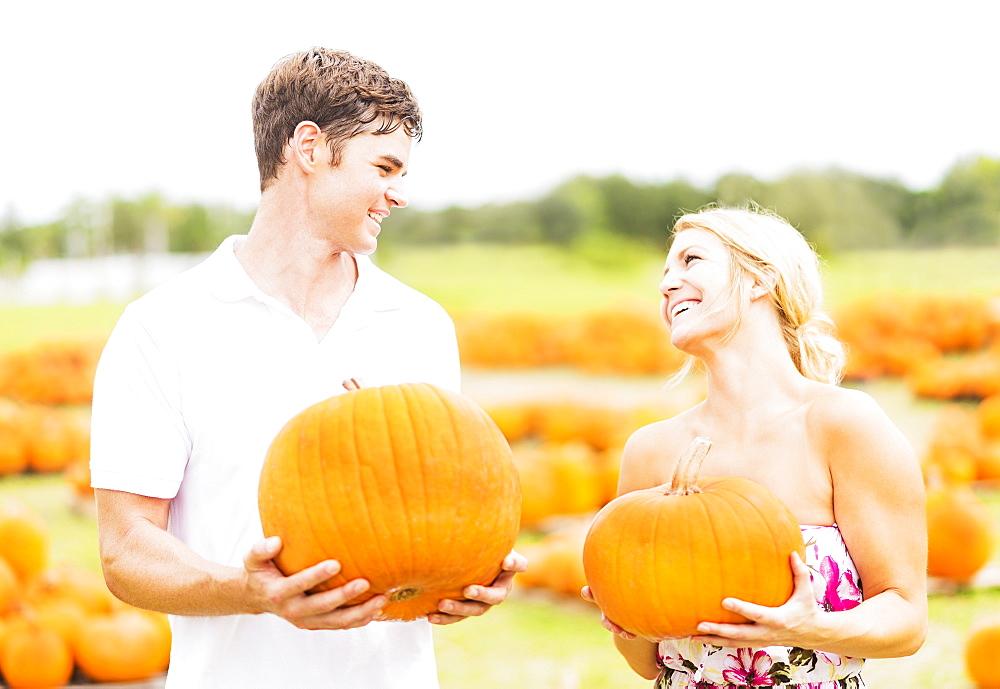 Portrait of young couple holding pumpkins, Jupiter, Florida