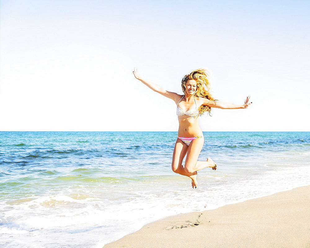 Portrait of young woman wearing bikini jumping on beach, Jupiter, Florida