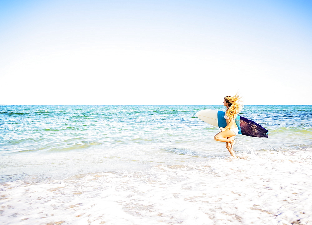 Young woman running in surf into sea carrying surfboard, Jupiter, Florida