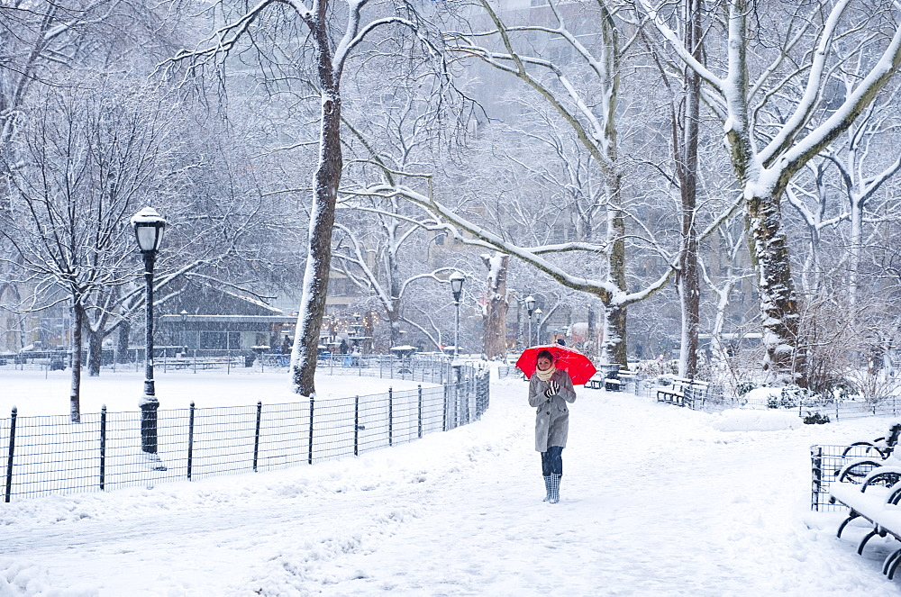 Woman walking with red umbrella on a snowy day