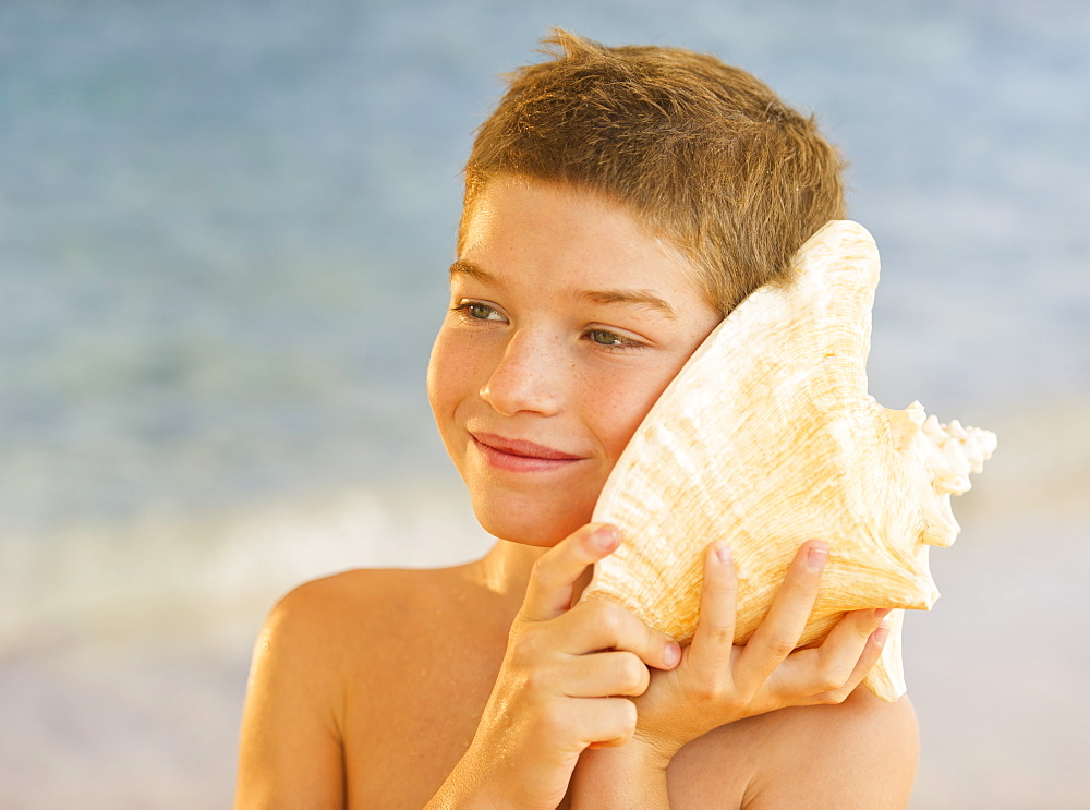 Boy (10-11) listening to sea shell on beach