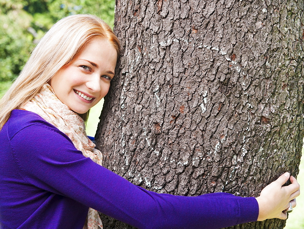 USA, New York, New York City, Manhattan, Central Park, Young woman embracing tree