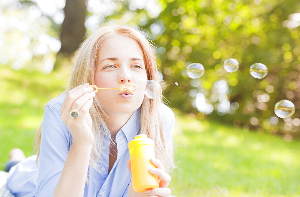 USA, New York, New York City, Manhattan, Central Park, Woman blowing bubbles