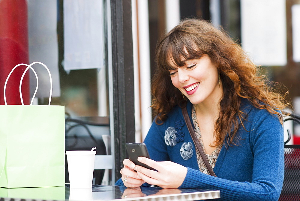 Woman sitting in sidewalk cafe and texting on mobile phone