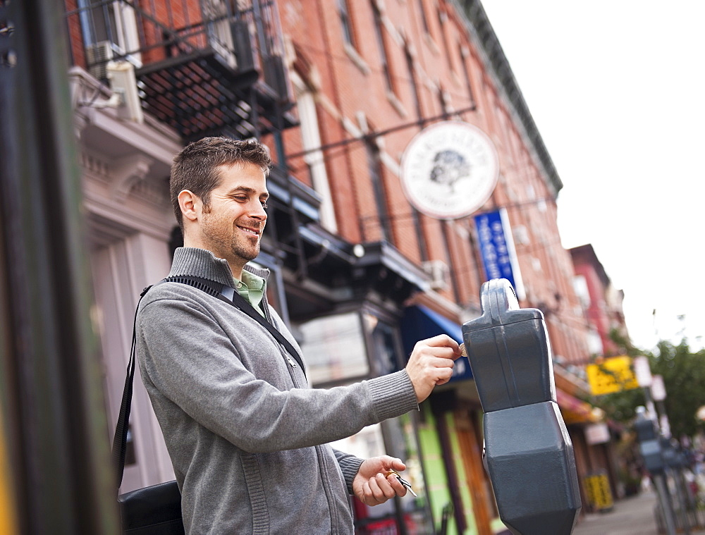 Man inserting coin to parking meter