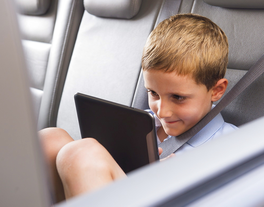 Boy (6-7) using digital tablet while sitting in car