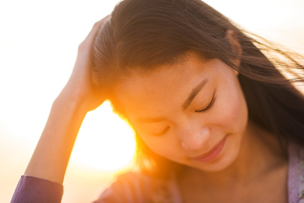Close-up of smiling teenage girl ( 16-17 years) with sunset in background