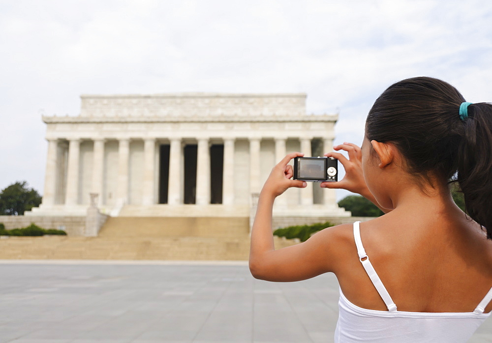 USA, Washington DC, girl (6-7) photographing Lincoln Memorial