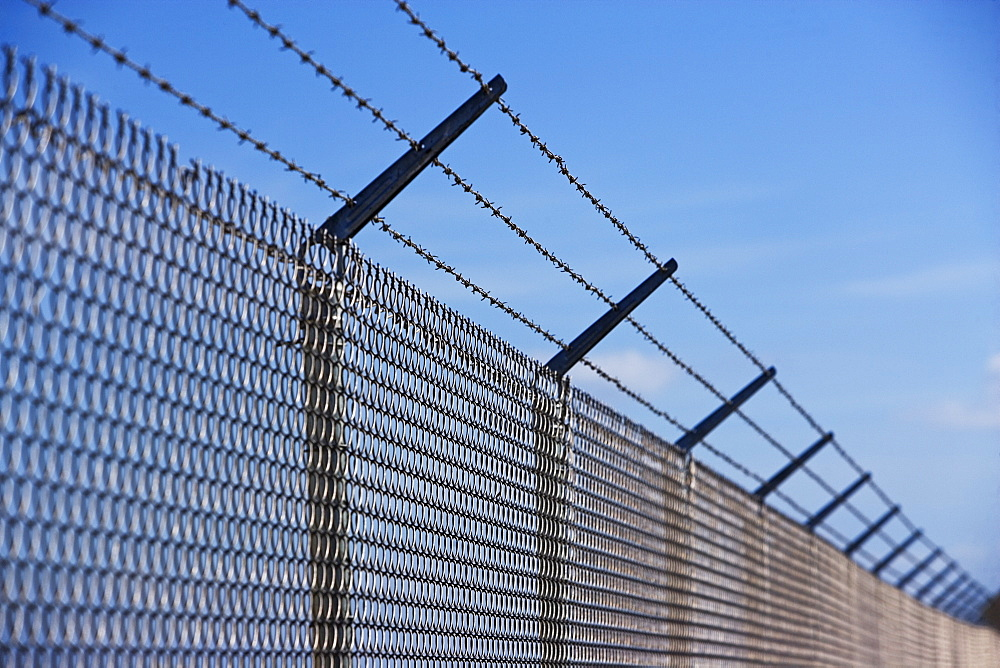 Metal fence with barbed wire