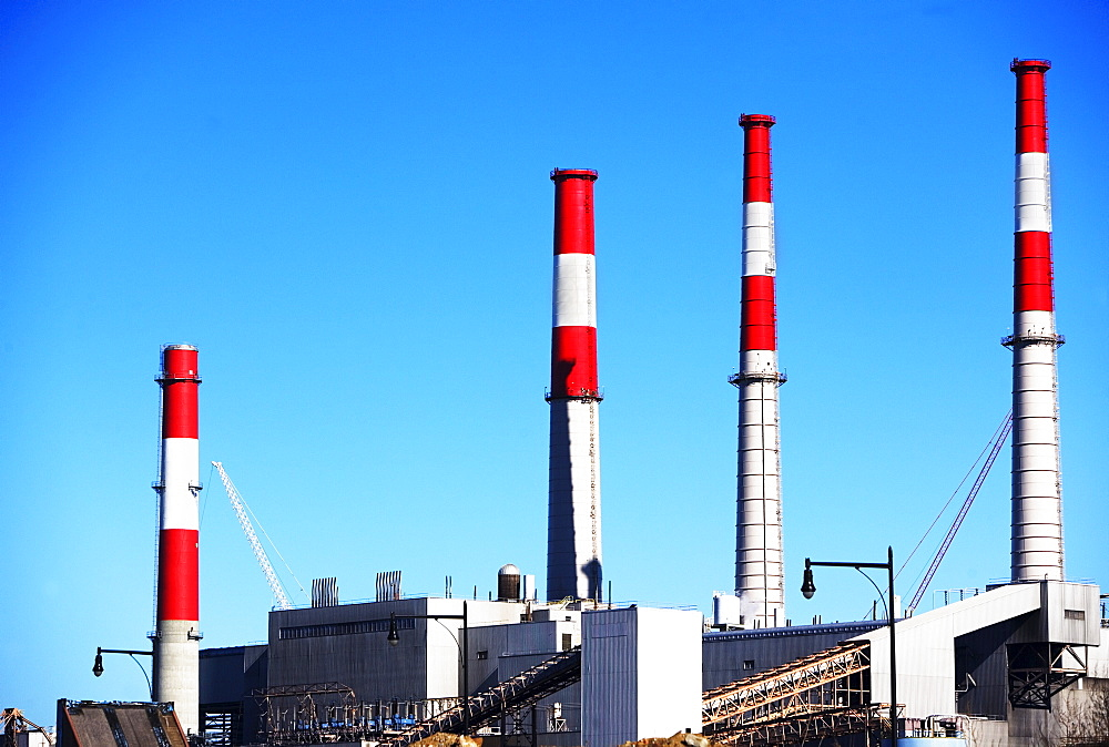 Factory with smoke stacks under blue sky