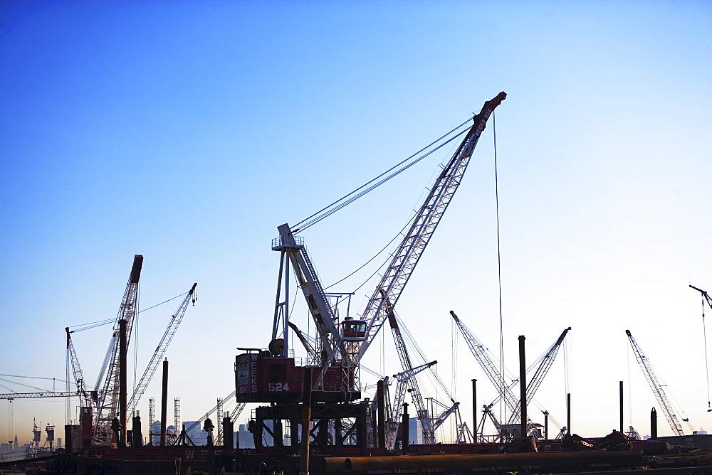Cranes on dock at sunset