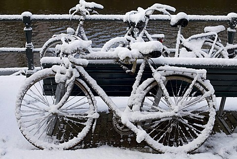 Snow covered bicycle parked on bridge, Netherlands, Amsterdam