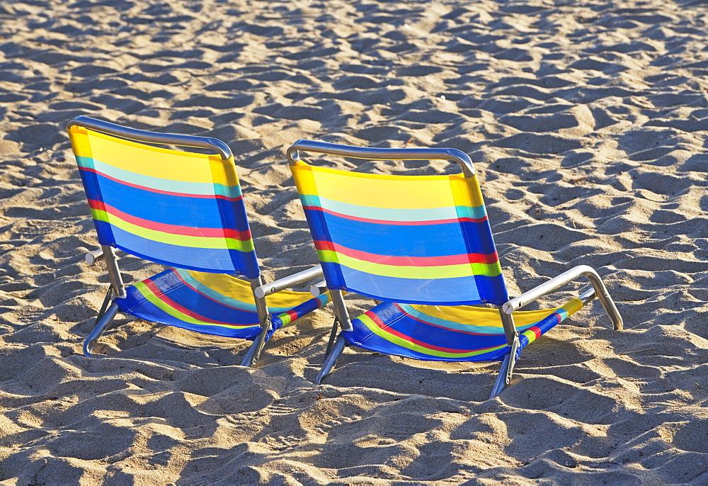 Empty beach chairs on sand