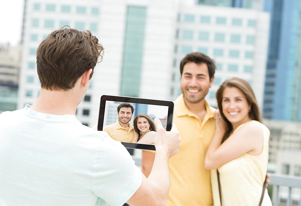 Man using tablet pc to take picture of friends