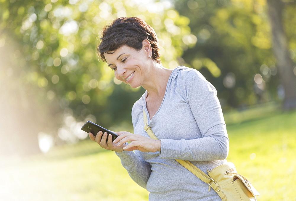 Mature woman text messaging outdoors