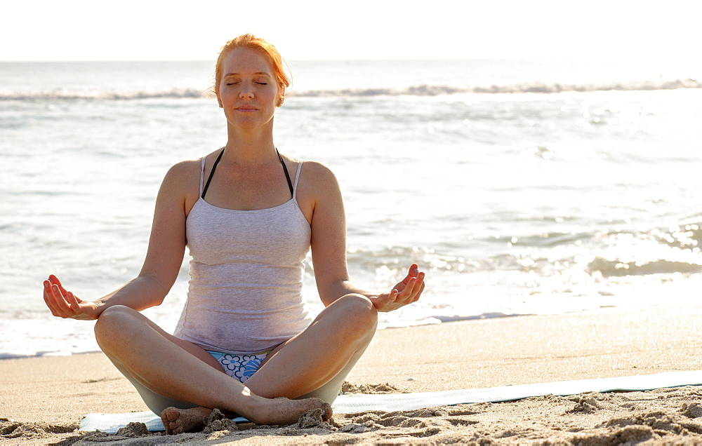 Woman practicing yoga on beach, Palm Beach, Florida