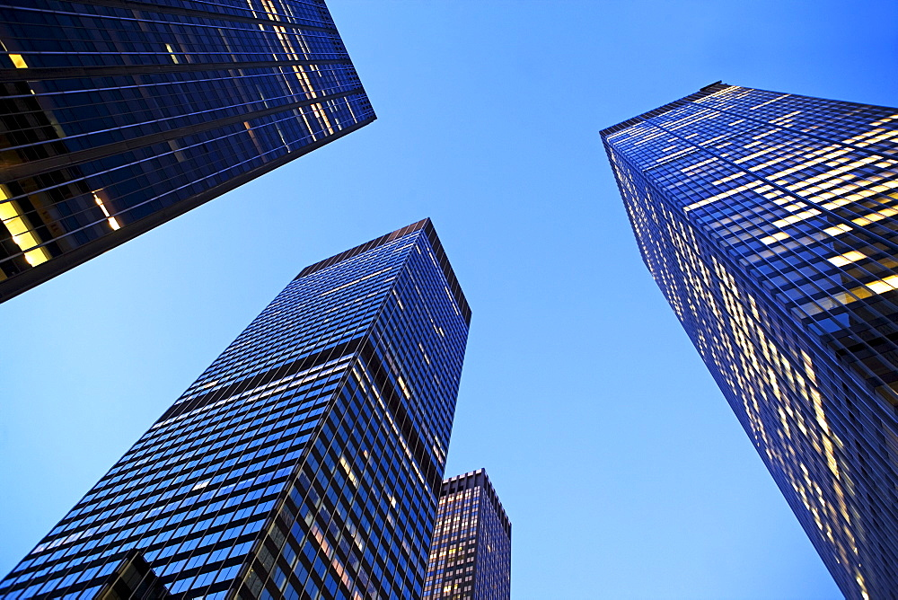 USA, New York State, New York City, Manhattan, low angle view of office buildings illuminated at dusk