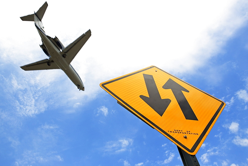 Airplane flying above down traffic sign