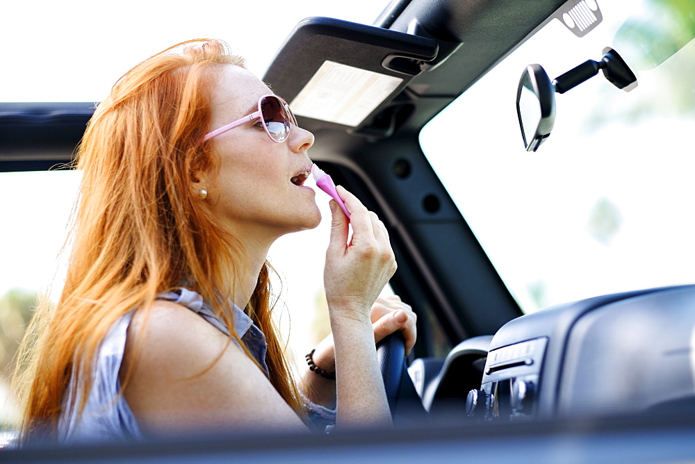 Woman doing make up in car