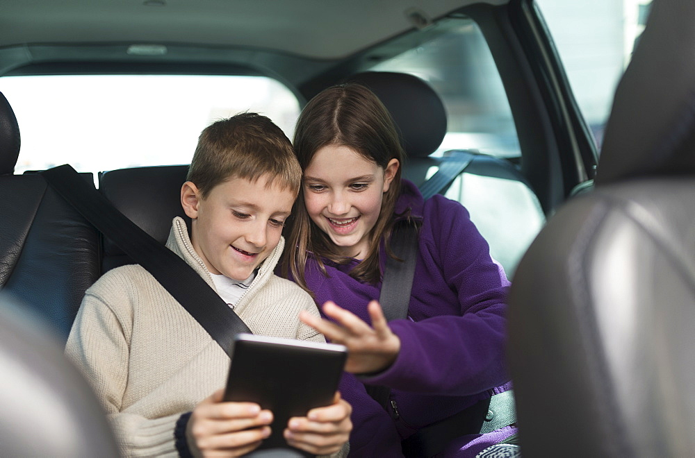 Boy and girl (8-9, 10-11) using digital tablet in car