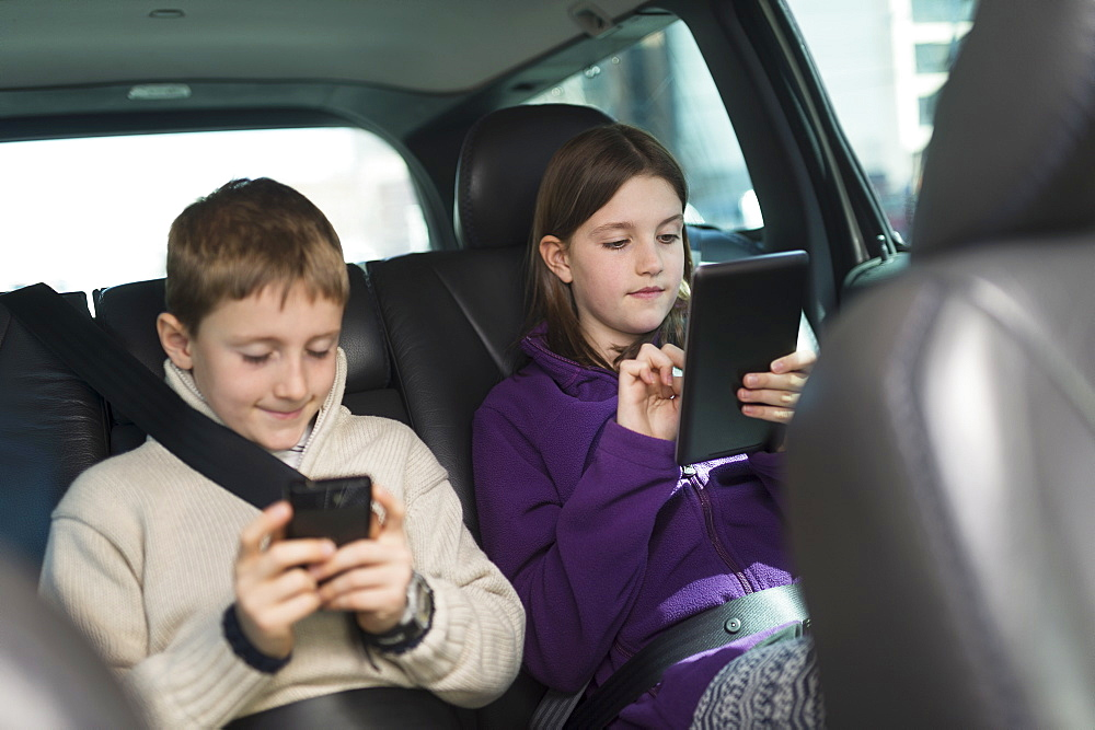 Boy and girl (8-9, 10-11) using digital tablet and smart phone in car
