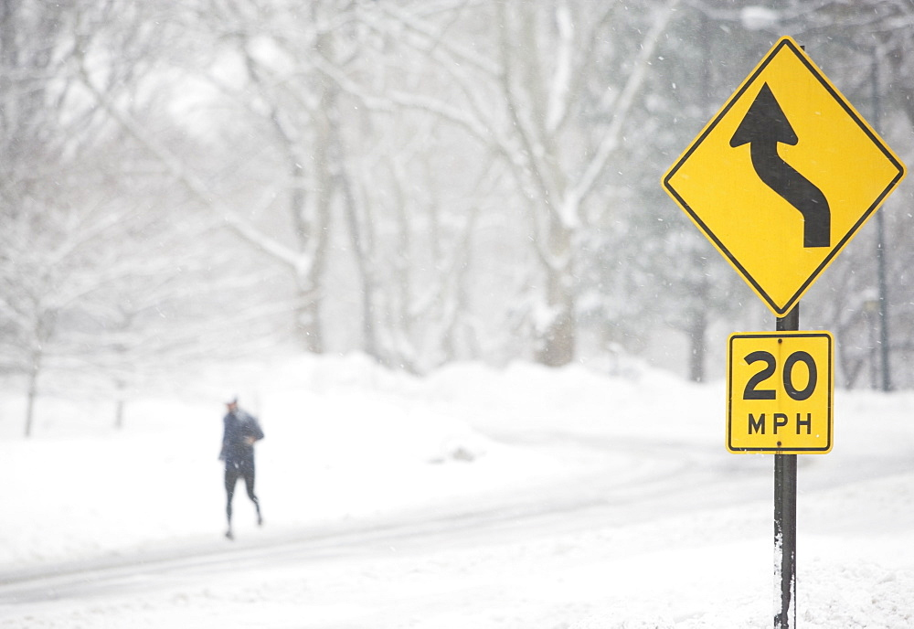 USA, New York City, speed limit and warning sign by snowy road