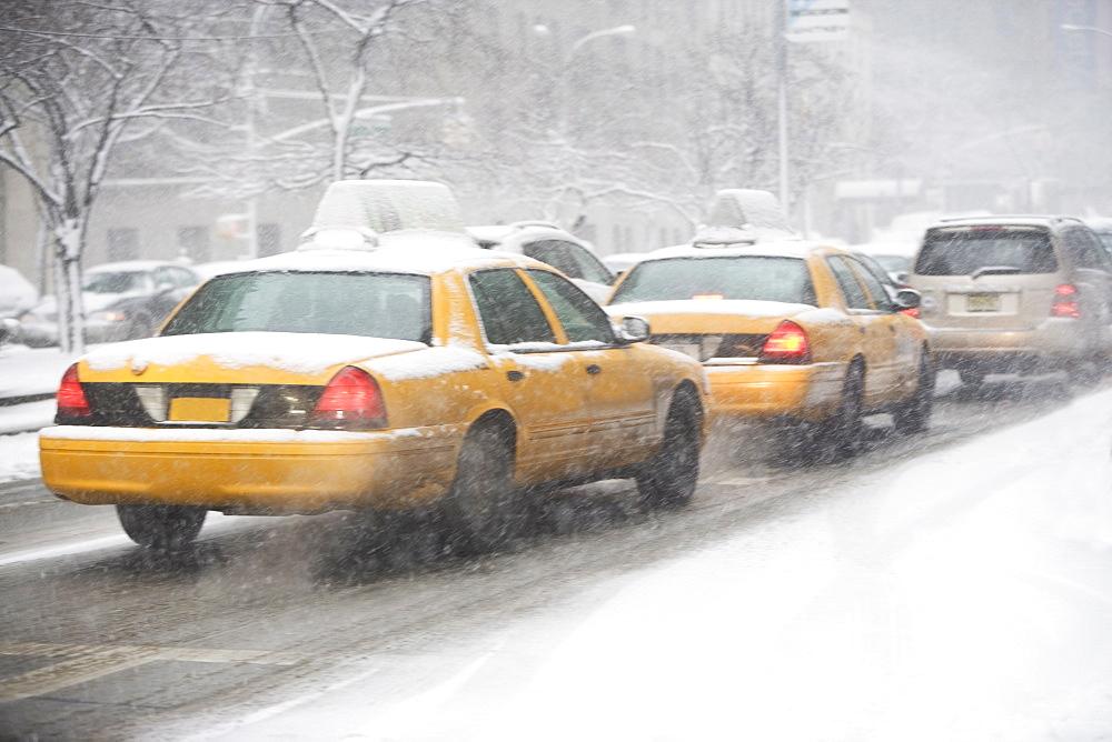 USA, New York City, yellow cabs on snowy street