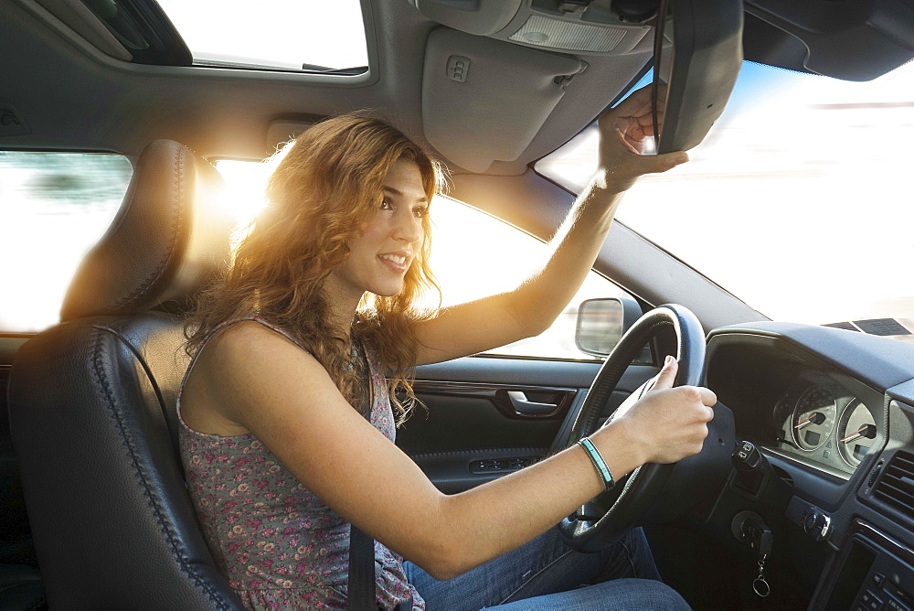 Young woman adjusting rear view mirror while driving