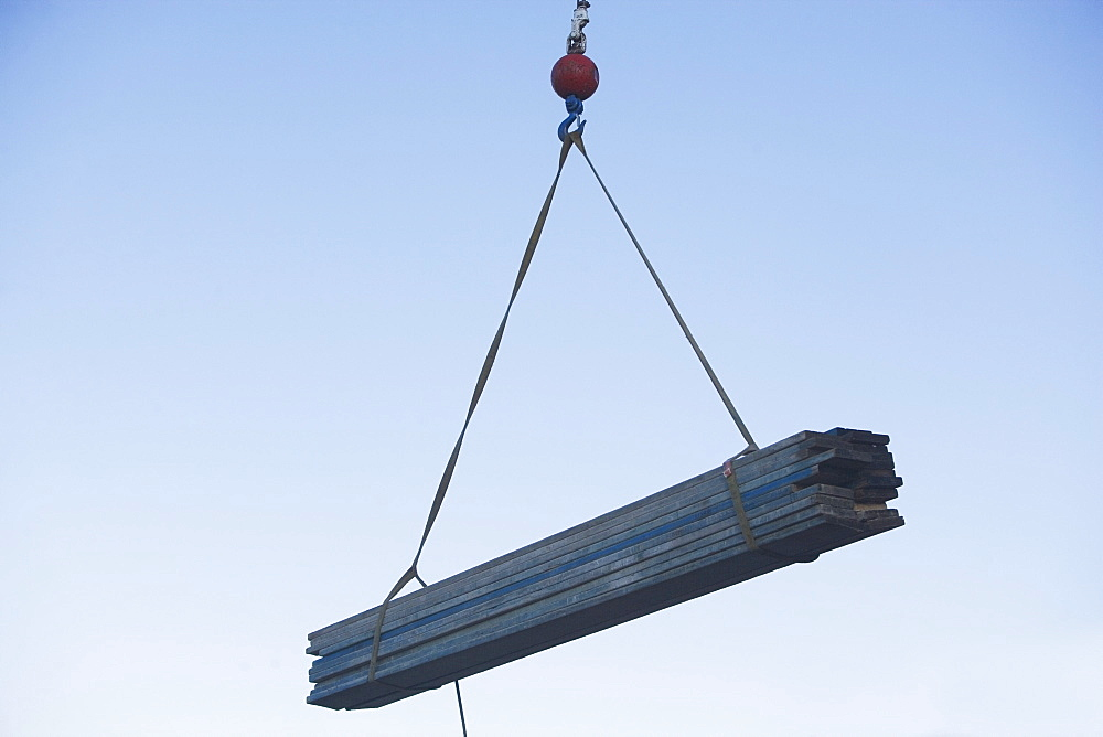 Mid-air view at crane's hook lifting wooden planks