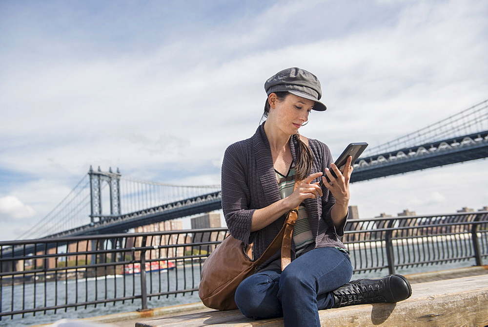 Woman using tablet pc, Manhattan Bridge in background, Brooklyn, New York