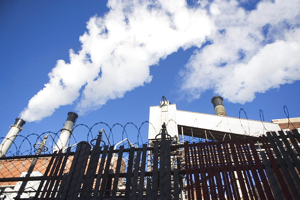 low angle view of factory chimneys behind fence