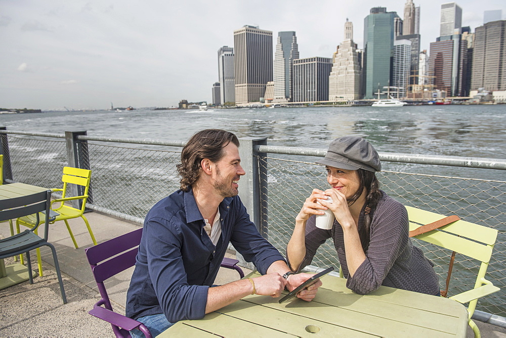 Happy couple sitting and using tablet pc and drinking coffee with cityscape in background, Brooklyn, New York