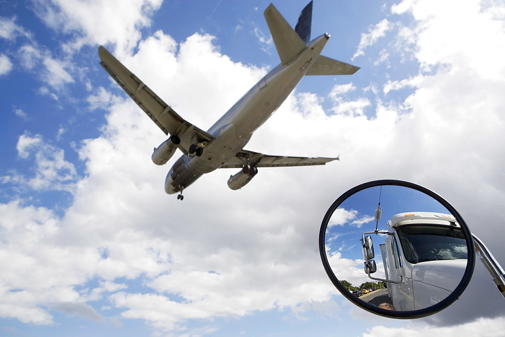 Reflection of semi-truck in side view mirror with plane flying above