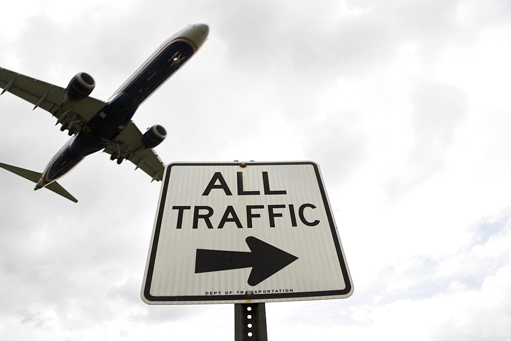 Airplane flying above road signs