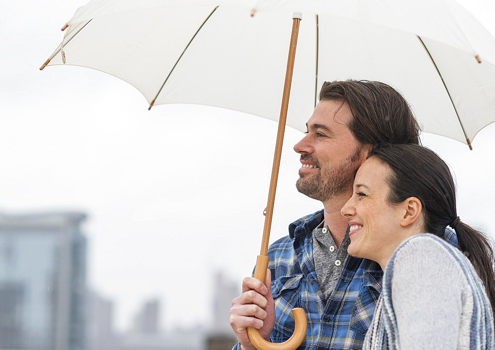 Side view of couple under umbrella