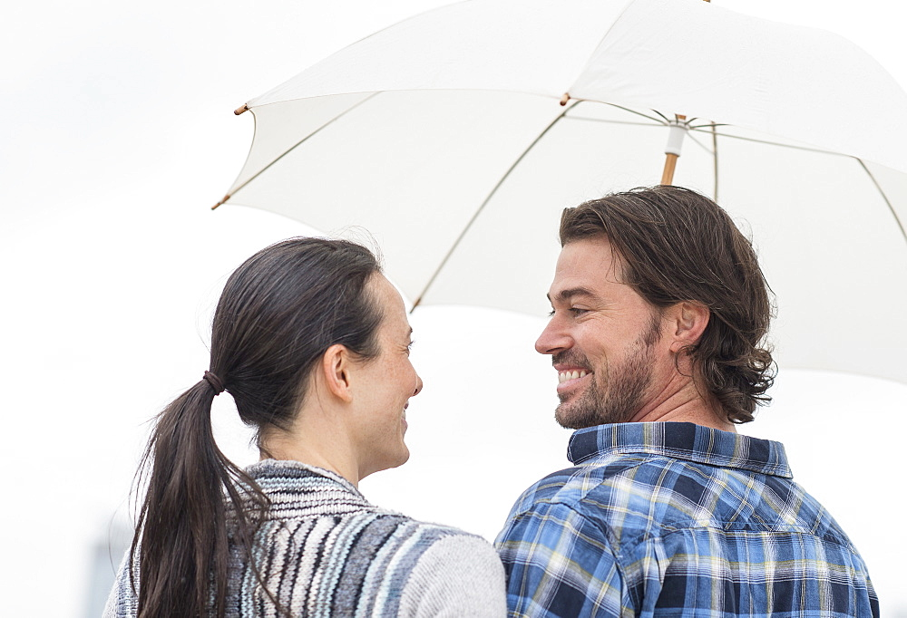 Rear view of couple under umbrella