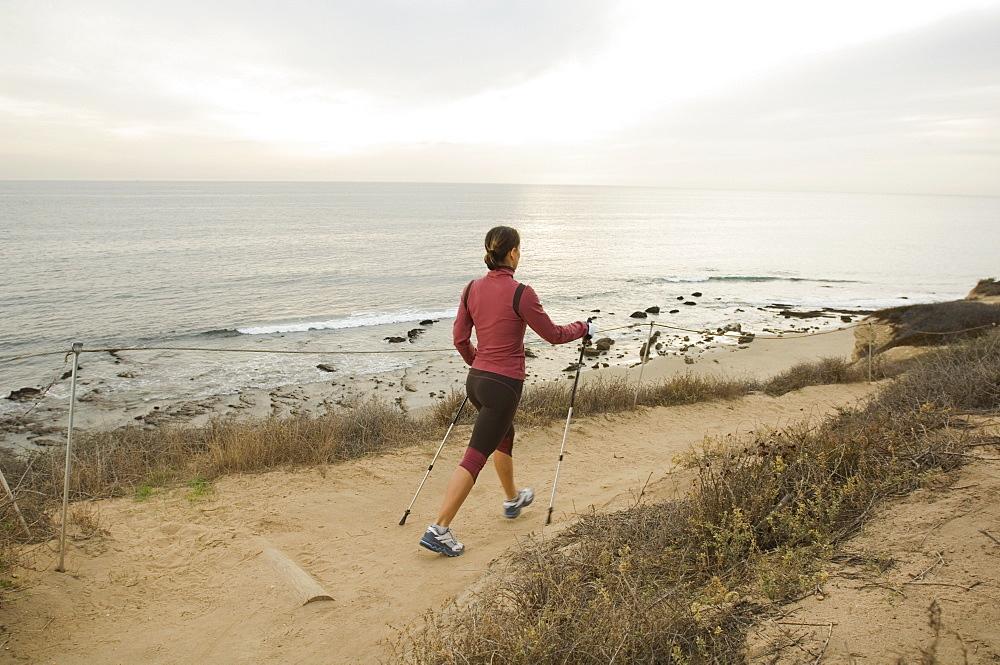 Hispanic woman pole walking along coast in California, United States