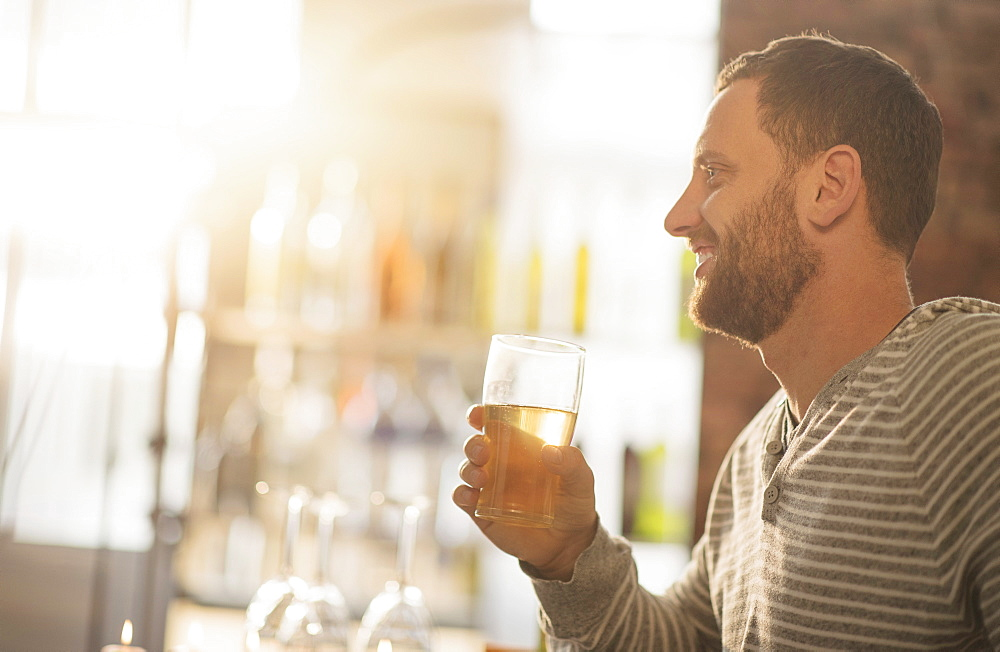 Side view of man having drink in bar