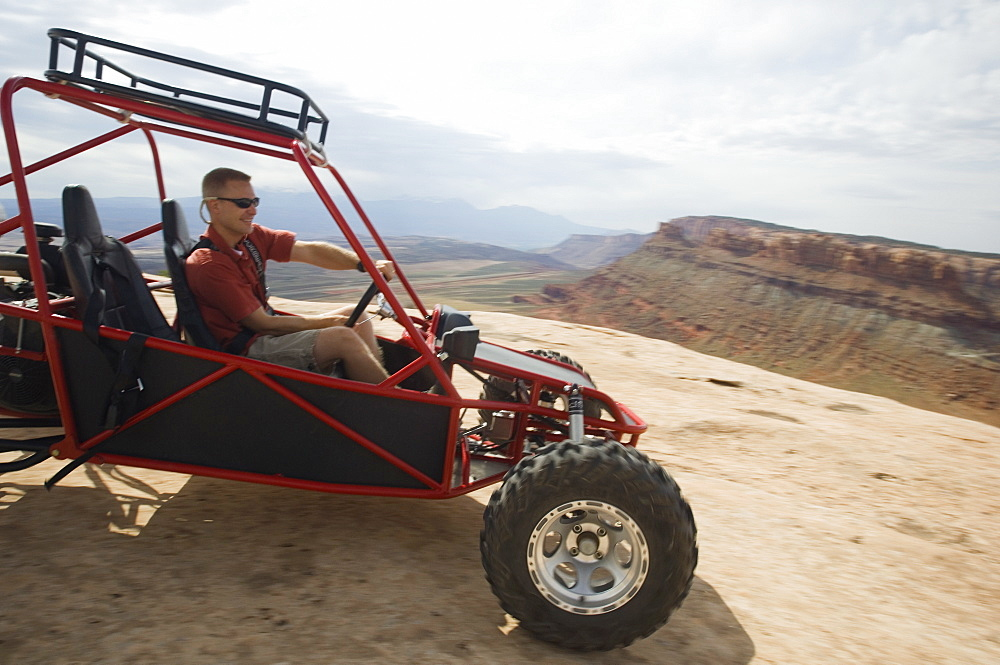 Man in off-road vehicle on rock formation