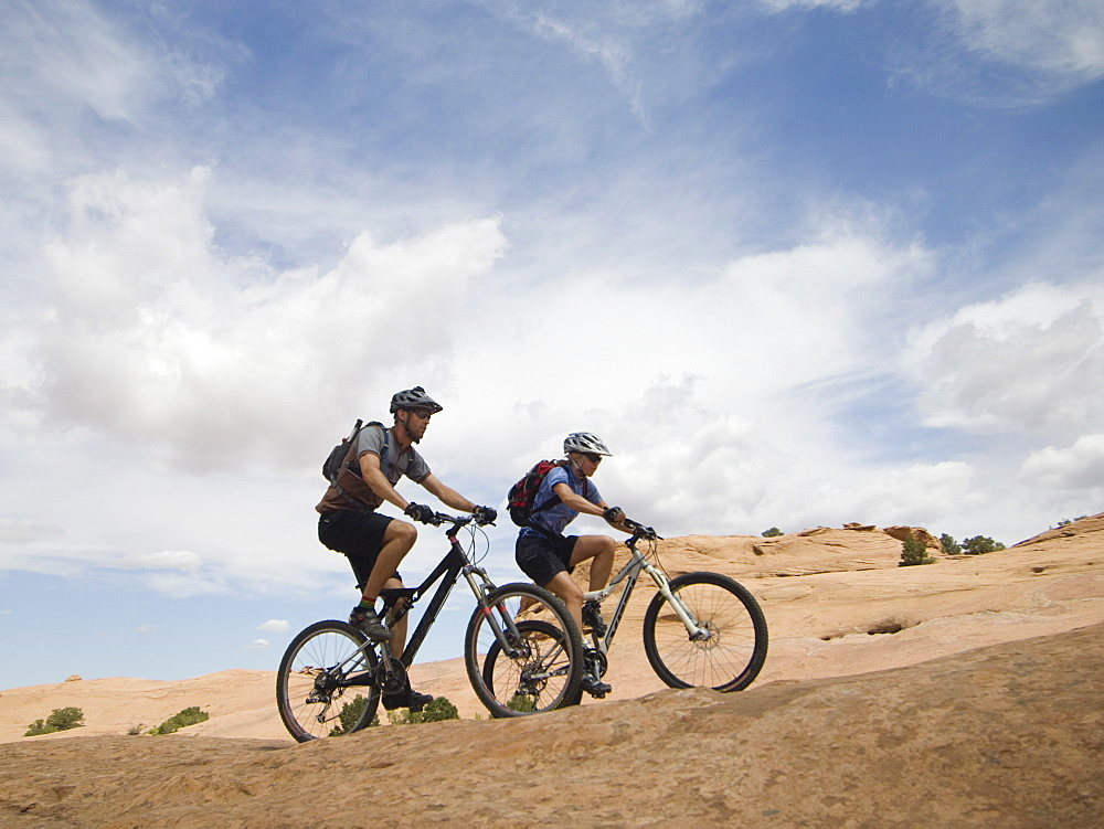 Couple riding mountain bikes in desert