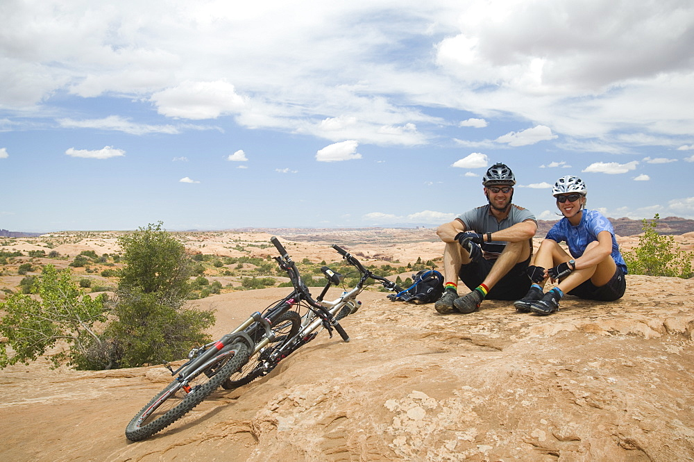 Cyclists sitting next to mountain bikes in desert